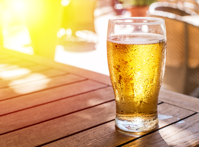 A beer sitting on an outdoor table in the warm sunlight