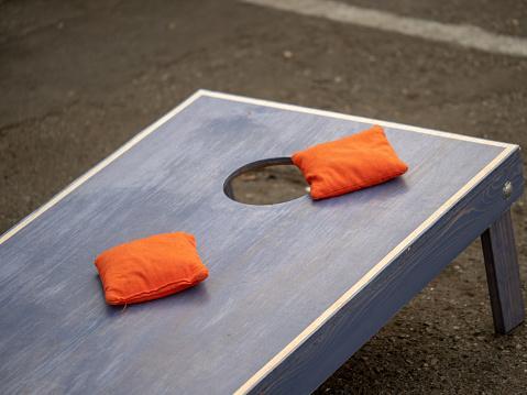 Orange beanbags sitting on blue cornhole board platform in middle of game